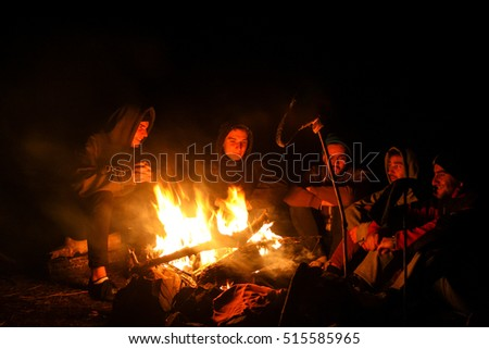 October 2014: group of friends laughing and sitting at camp fire after long autumn mountain hike