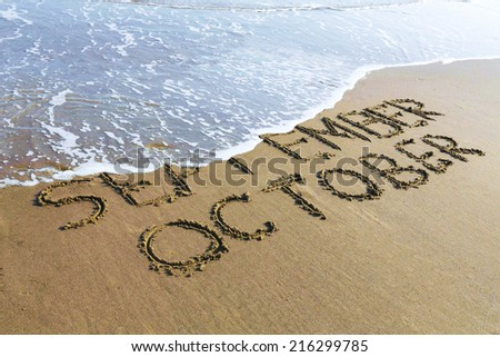 October is coming concept - inscription September and October written on a sandy beach, the wave is starting to cover the word September. - stock photo