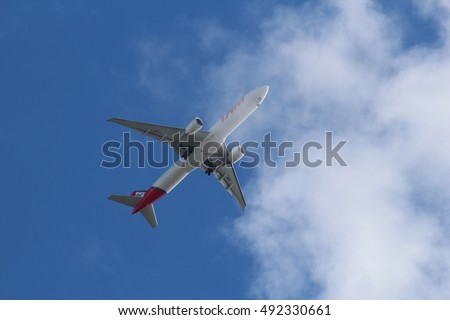 October 2016, London. A passenger airliner operated by Brazilian airline LATAM Airlines Brasil, formerly TAM Airlines, flies through a cloudy sky over South West London
