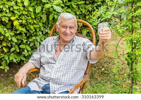 octogenarian elder in checkered shirt is happy while playing cards in the garden of his house in the Italian countryside