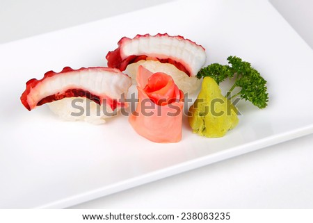 octopus and grape seaweed on white disk. - stock photo