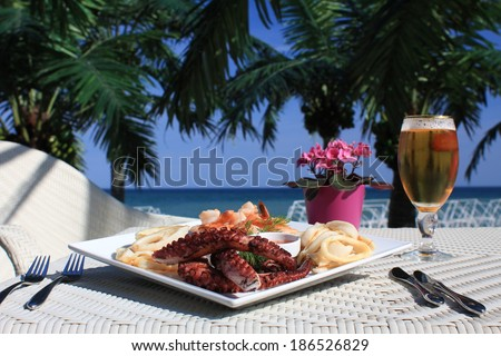octopus in dish on the beach. Table set and beer - stock photo