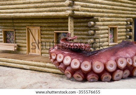 Octopus nightmare on old log cabin home. - stock photo