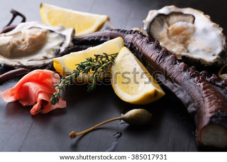 Octopus, oysters with lemon, thyme and ginger on a dark background - stock photo