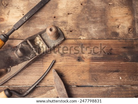 Od vintage hand tools on wooden background. Carpenter workplace.  Tinted photo - stock photo