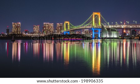 ODAIBA, JAPAN -DECEMBER 29, 2013 : Rainbow bridge reflected in the water at night