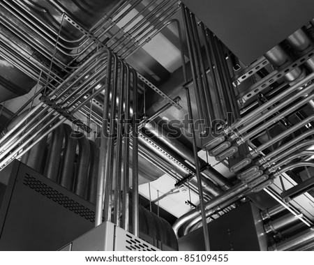 Odd angles of electrical conduits captured in black and white.  Taken in an industrial building. - stock photo