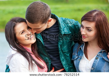 Odd man out. Young teenage couple outdoor - stock photo