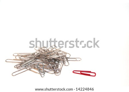 Odd One Out Concept with paper clip pile and single paperclip.  Space for copy. - stock photo