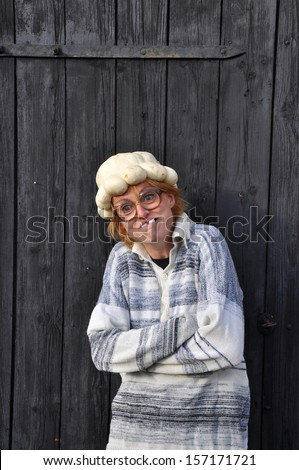 Odd woman with a pumpkin on her head in front of a black barn door. - stock photo