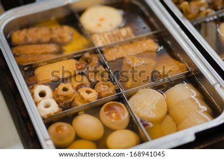 Oden, popular Japanese winter hodge-podge-like cuisine of daikon radish, konnyaku, and fish cakes, being stewed in a light, soy-flavoured dashi broth at a street stall  - stock photo