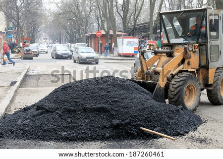 Odessa - April 3: a team of workers repairs road under the program of urban planning repairs after winter frosts that destroyed an asphalt road . April 3, 2014 in Odessa, Ukraine