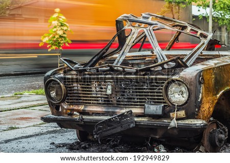 ODESSA - MAY 14: Front view of burned car on road with car traffic on a background on May 14, 2014 in Odessa, Ukraine. Abandoned car was exploded at night time on May 10, 2014. Long exposure shot. - stock photo