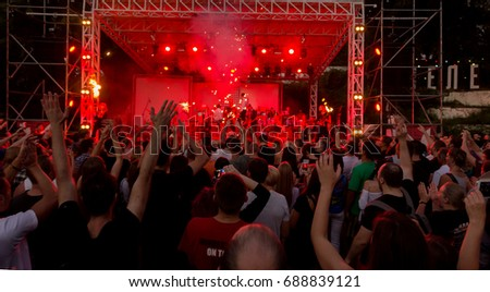 ODESSA, UKRAINE August -1, 2017: fans are enjoying concert in fan zone of hall during concert of hamlet-metal band Rammstein. crowd of people silhouettes with their hands up. Selective focus