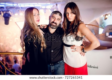 Odessa, Ukraine August 23, 2014: Ibiza club. People smiling and posing on cam during concert in night club party. Man and woman have fun at club. Boy and girl at night club party