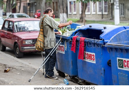 Odessa, Ukraine -15 August 2016: Lame homeless tramp near the garbage cans looking for empty bottles and leftover food. The problem of homeless people during the economic crisis - stock photo