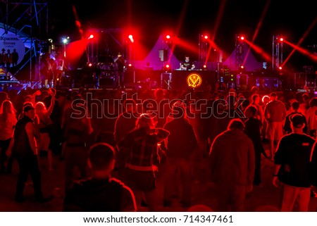 ODESSA, UKRAINE-August 25, 2017: large crowd of spectators, fans of rock concert during music show during day. Spectators in sand of beach during festival of music and sports Z-games. Selective focus