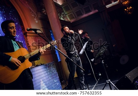 Odessa, Ukraine December 31, 2015: Artist performs songs from stage during concert at nightclub. Artist on club stage during night party.