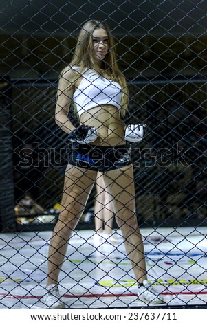 Odessa, Ukraine - December 13: MMA fighters in mixed martial arts competition in the cell. Beautiful girls entertain guests, December 13, 2014 in Odessa, Ukraine - stock photo