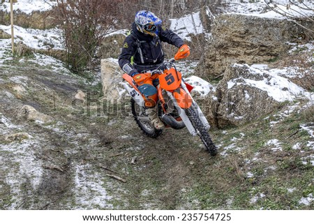 Odessa, Ukraine - December 6, 2014: Off-road motorcyclist on motocross off-road route passes in winter mountains, December 6, 2014 in Odessa, Ukraine.