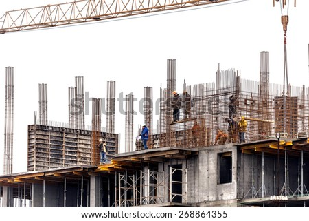 Odessa, Ukraine -13 December 2014: Workers at a construction site high-rise building are assembling and welding work in the evening and at night. Building silhouette against the sky. - stock photo