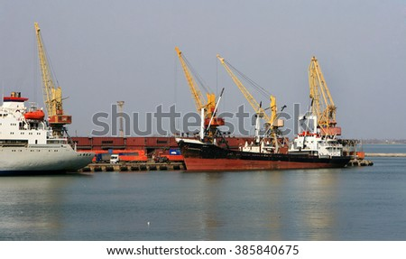 Odessa, Ukraine - 28 February 2010: Container cranes in port container terminal. Industrial cargo ship is loaded at seaport. Loading operations. Sea trading port