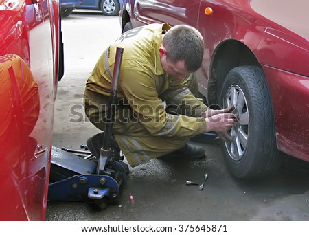 Odessa, Ukraine, February 10, 2016 -: Mechanic changing a punctured car tire on the road in the city.