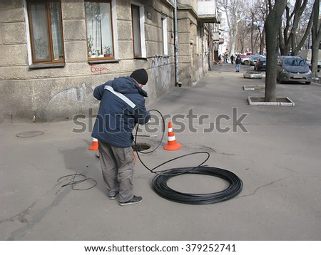 Odessa, Ukraine, 16 February 2016 -: Workers paving urban highway engineering. Modern techniques performed repair and replacement of electrical networks and cable laying modern optical communication.