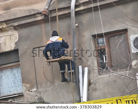 Odessa, Ukraine, February 12, 2016 -: Workman Replacing Guttering On Exterior Of House in Odessa city center
