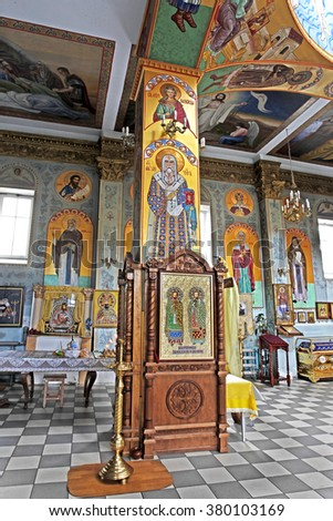 Odessa, Ukraine: Interior of the Orthodox Church, altar, iconostasis, and beautiful historic architectural arches, painted icons, frescoes, bas-reliefs in natural light, gilding