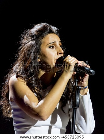 "ODESSA, UKRAINE - July 16, 2016: Ukrainian singer Jamala at solo concert at Opera House. Delighted fans in hall. Jamal won 61st annual Eurovision Song Contest with song ""1944"" in Stockholm in 2016."