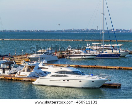 Odessa, Ukraine July 6, 2016: Yacht Club with parked vehicles of various models. Pleasure boat with tourists depart from the pier in Odessa, Ukraine, July 6, 2016