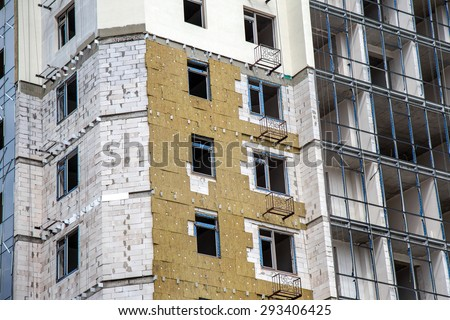 ODESSA, UKRAINE - JUNE 18 2014: Construction of high-rise residential building works on the outer facade of building insulation, insulation. Modern technology in the construction of thermal insulation