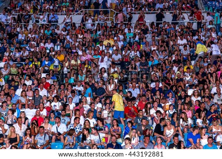 Odessa, Ukraine - June 25, 2016: large crowd of spectators having fun at stadium, at a concert of Ukrainian group Ocean Elzy during creative light and music show. Cheerful bright show in party club