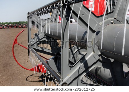 ODESSA, Ukraine June 11, 2010: New combine harvesters lined up in a long row at the exhibition - sale of pre-season harvest of the new crop. Working mechanisms combine close-up. Selective Focus - stock photo