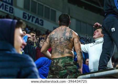ODESSA, UKRAINE - March 24, 2016: Football fans and spectators in stands of stadium emotionally support their team during match of national team of Ukraine and Cyprus. Emotions, torches, smoke, cries - stock photo
