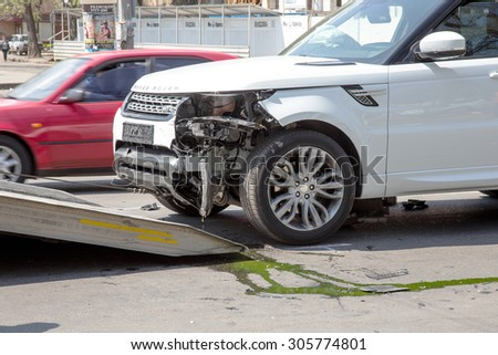 Odessa, Ukraine - May 3, 2015: A car accident in the city center. expensive car was loaded onto a tow truck after a car accident.  - stock photo
