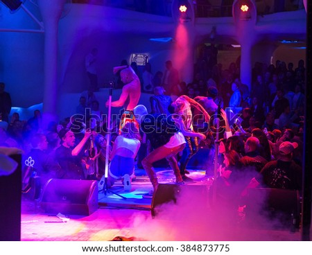Odessa, Ukraine -17 May 2015: a large crowd of people having fun in a nightclub at a concert during the creative light and music show. Cheerful young people, candy and smoke on a club party.