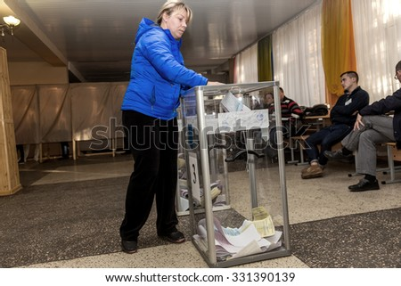Odessa, Ukraine - 25 October 2015: a polling station during the elections of regional political local deputies and mayors. The voters take the ballots and cast into the sealed ballot box.