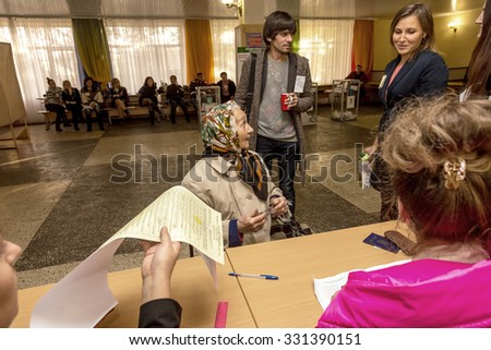 Odessa, Ukraine - 25 October 2015: a polling station during the elections of regional political local deputies and mayors. The voters take the ballots and cast into the sealed ballot box. - stock photo