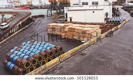 Odessa, Ukraine - October 13, 2016: Industrial products, raw materials, timber and sheet steel mill in the industrial port quay shopping ready for loading cargo seagoing vessels