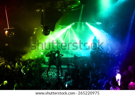 Odessa, Ukraine - October 2, 2011: Large crowd of people having fun in a nightclub at concert during creative light and music show. Cheerful young people, candy and smoke on club party. creative light
