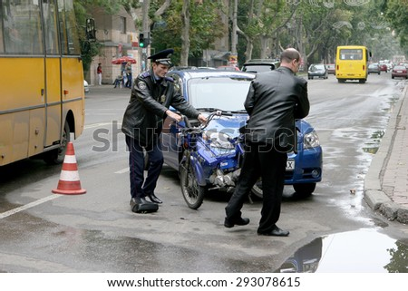 Odessa, Ukraine - October 4, 2008: Light accident between a car and a motorcycle. Bike crashed into a car. He lost control on the wet asphalt. Powered Police - stock photo