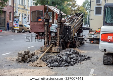 Odessa, Ukraine -October18,2015: Modern technologies. Installation plastic pipe by drilling point under highway. Pulling cable and pipe drilled underground Stroebe. Modern complex laying plastic pipes