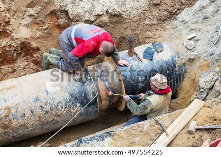 Odessa, Ukraine - October 11, 2016: Repair of heating duct. The workers, welders made by electric welding and gas welding on large iron pipes at a depth of excavated trench.