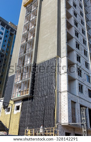 Odessa, Ukraine - October 16, 2015: Work on insulation of facades high-rise apartment building. Warming houses, house wall insulation, waterproofing the walls of house. Modern construction technology