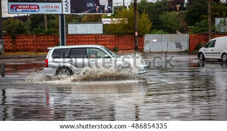ODESSA, UKRAINE - September 20, 2016: Cars driving on a flooded road during flooding caused by torrential rains. Cars float on water flooded streets