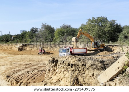 Odessa, Ukraine - September 14, 2015: Construction site at digging the pit. Preparatory work for the construction of grain silos. The work of construction machinery in a quarry - stock photo