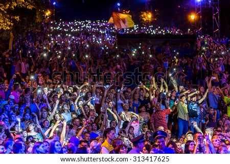 Odessa, Ukraine - September 2, 2015: The audience at concert during the creative light and music show fashionable jazz orchestra. Night scene, audience emotionally watching, standing outside on stairs - stock photo