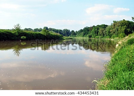 Odra river in protected area named Meandry Odry on czech-polish boundaries near Bohumin city during spring day with blue sky and clouds